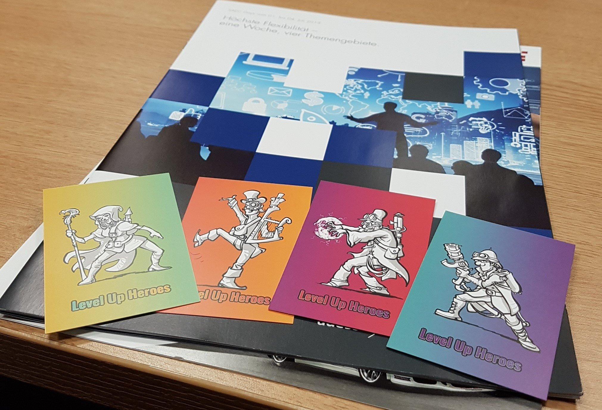 """Prospekt der Clean Code Days 2019. Darauf liegen vier Visitenkarten, auf denen jeweils eine gezeichnete Fantasy-Figur abgebildet ist mit dem Text """"Level Up Heroes"""" darunter."""